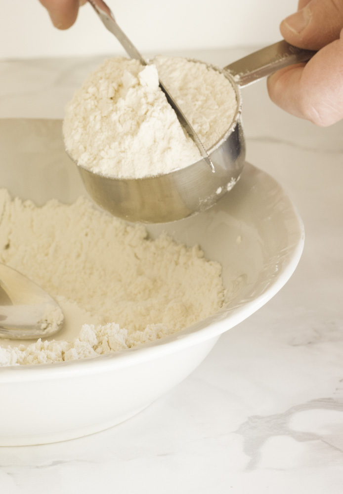 some flour in a bowl and flour in a measuring cup being leveled off with a knife