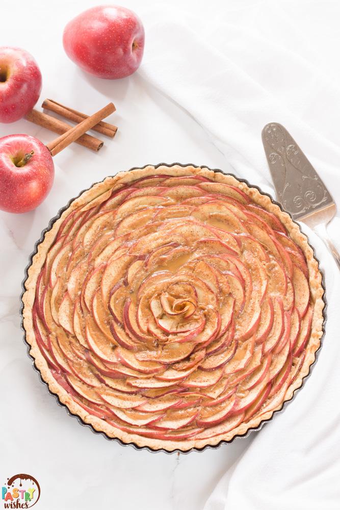 apple rose tart with kitchen towel, spatula, two apples and three cinnamon sticks