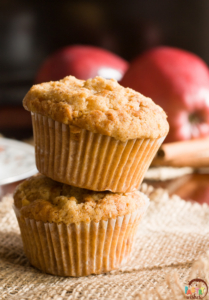 two streusel top apple mufins, one on top of the other, with two apples and cinnamon sticks