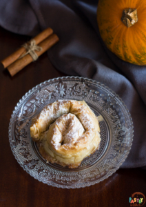 greek pumpkin hand pie on a plate with cinnamon sticks and a pumpkin