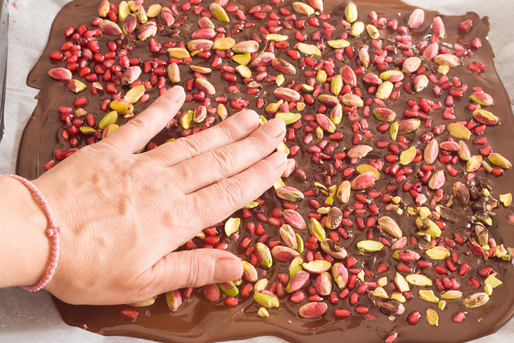 pressing pomegranate seeds and pistachios into melted chocolate