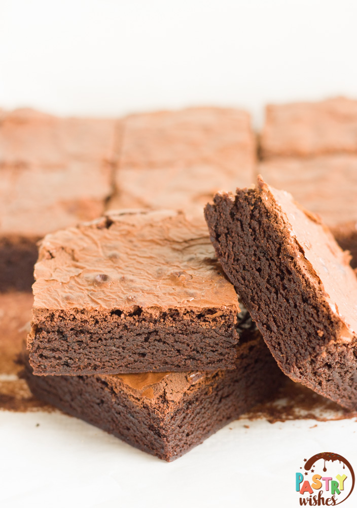 3 brownies piled together with sliced brownies in the background