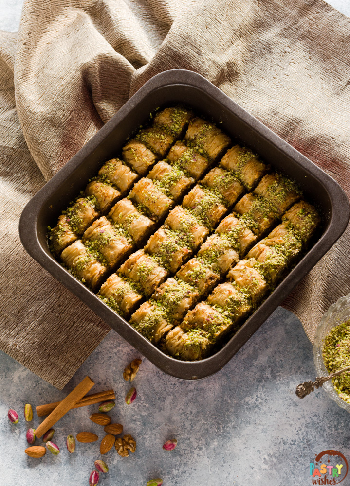 pan of saragli baklava rolls on wooden surface with nuts, cinnamon and bowl of grated pistachios