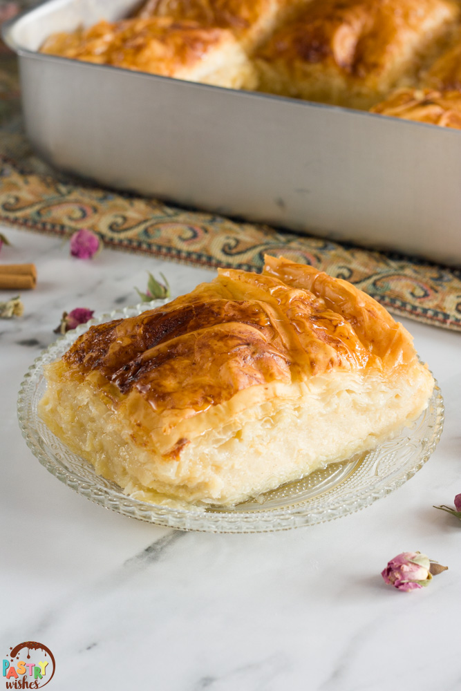 traditional greek custard pie galaktoboureko on a plate and in a pan on a white countertop with cinnamon sticks and dried roses