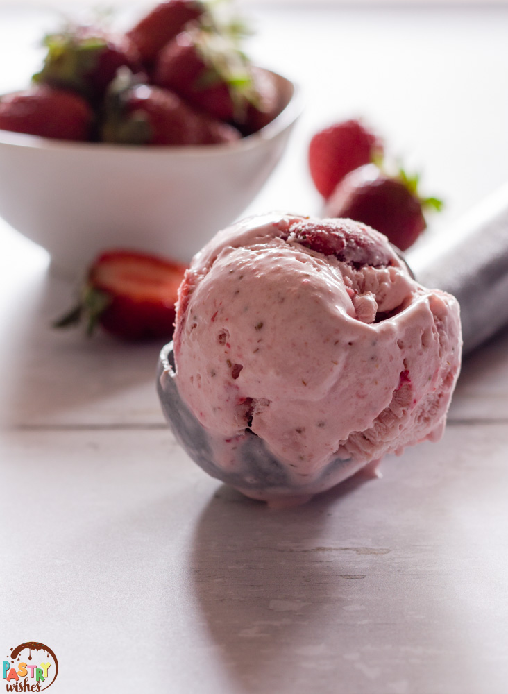 scoop of strawberry ice cream on a table with a bowl of strawberries in the background