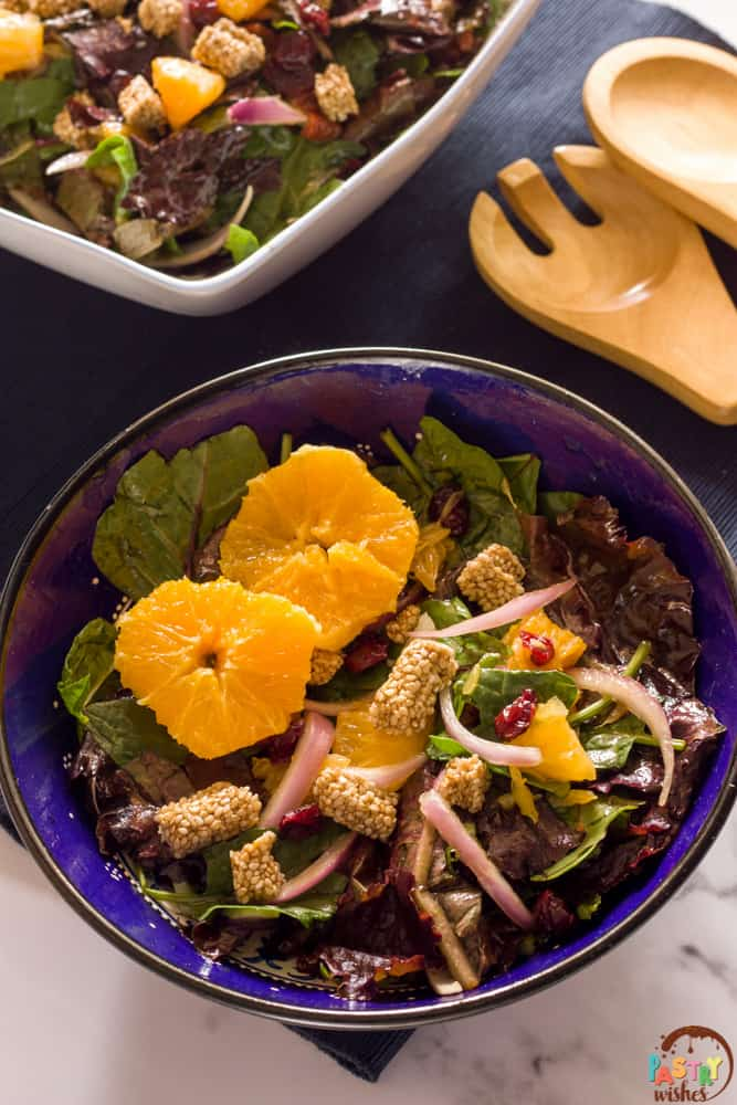 2 bowls of Greek pasteli salad with a blue mat and salad spoon