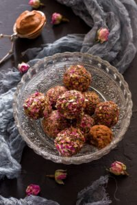 rose bliss balls in a glass bowl on a dark surface with dried rose buds