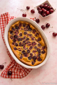 close up of cherry clafoutis in a white baking dish