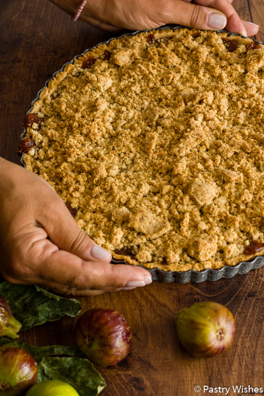 two hands holding a pan of fig crumble tart