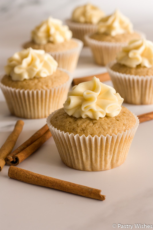 cinnamon cupcakes with maple cream cheese frosting on a white surface with cinnamon sticks
