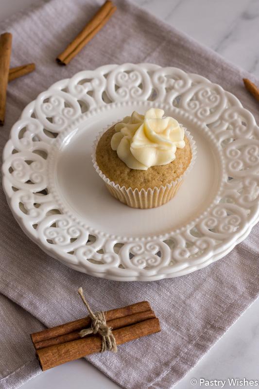 a cinnamon cupcake on a white plate on a napkin with cinnamon sticks