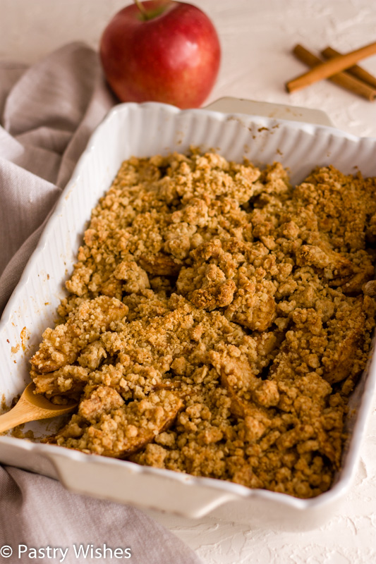 vegan apple crisp in a baking dish with an apple and cinnamon sticks in the background